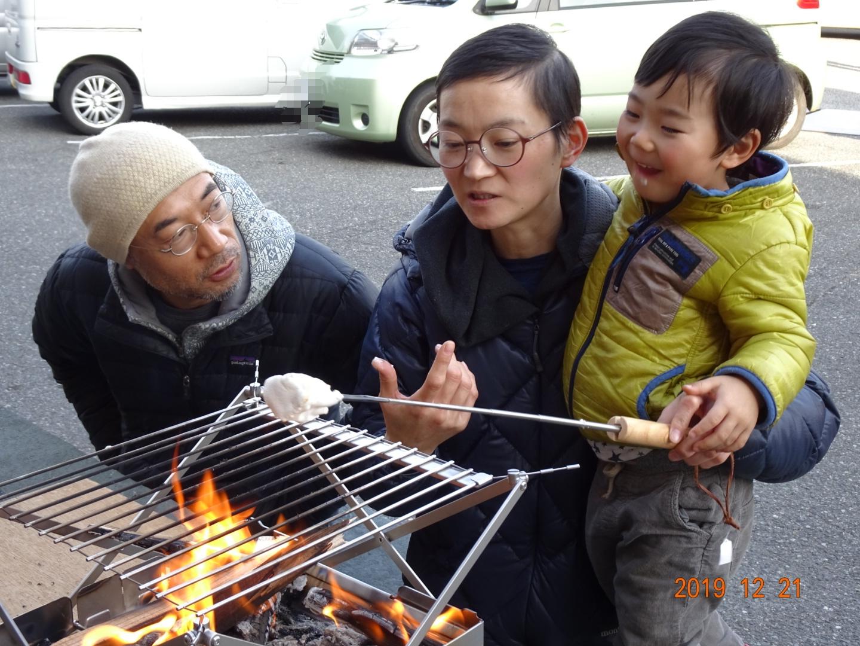焚き火で焼きマシュマロを作って楽しむ親子